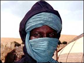 A white man dressed like an Algerian Tuareg; many Trinondevs of Weir dress similarly except all male Utopians are black; Trinondevs weild eye-staves; scanned in from a newpaper, photo attributed to Dan Cayo 2003